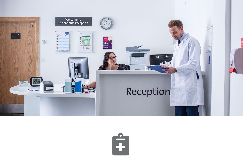 Krankenhausempfang mit weiblicher Sprechstundenhilfe im Gespräch mit Arzt im weißen Kittel und grauem Klemmbrett