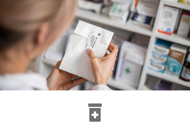 Apothekerin etikettiert Medikamente in Apotheke