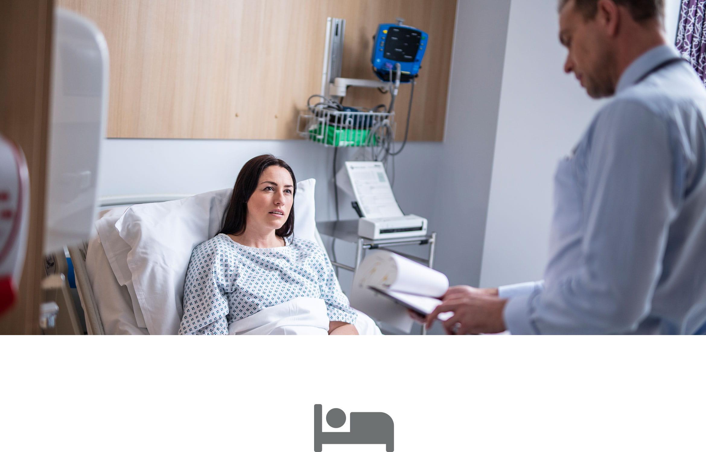 Patientin liegt im Klinikbett  Arzt schaut auf Patientennotizen