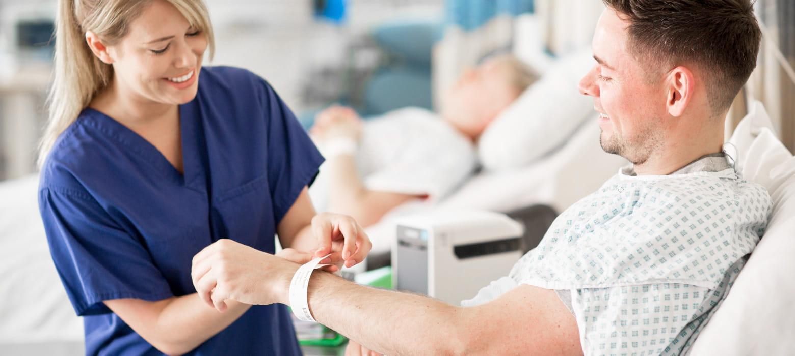 Krankenschwester, lächelnd, befestigt Patientenarmband an Arm von Patient, TD-2130NHC im Hintergrund