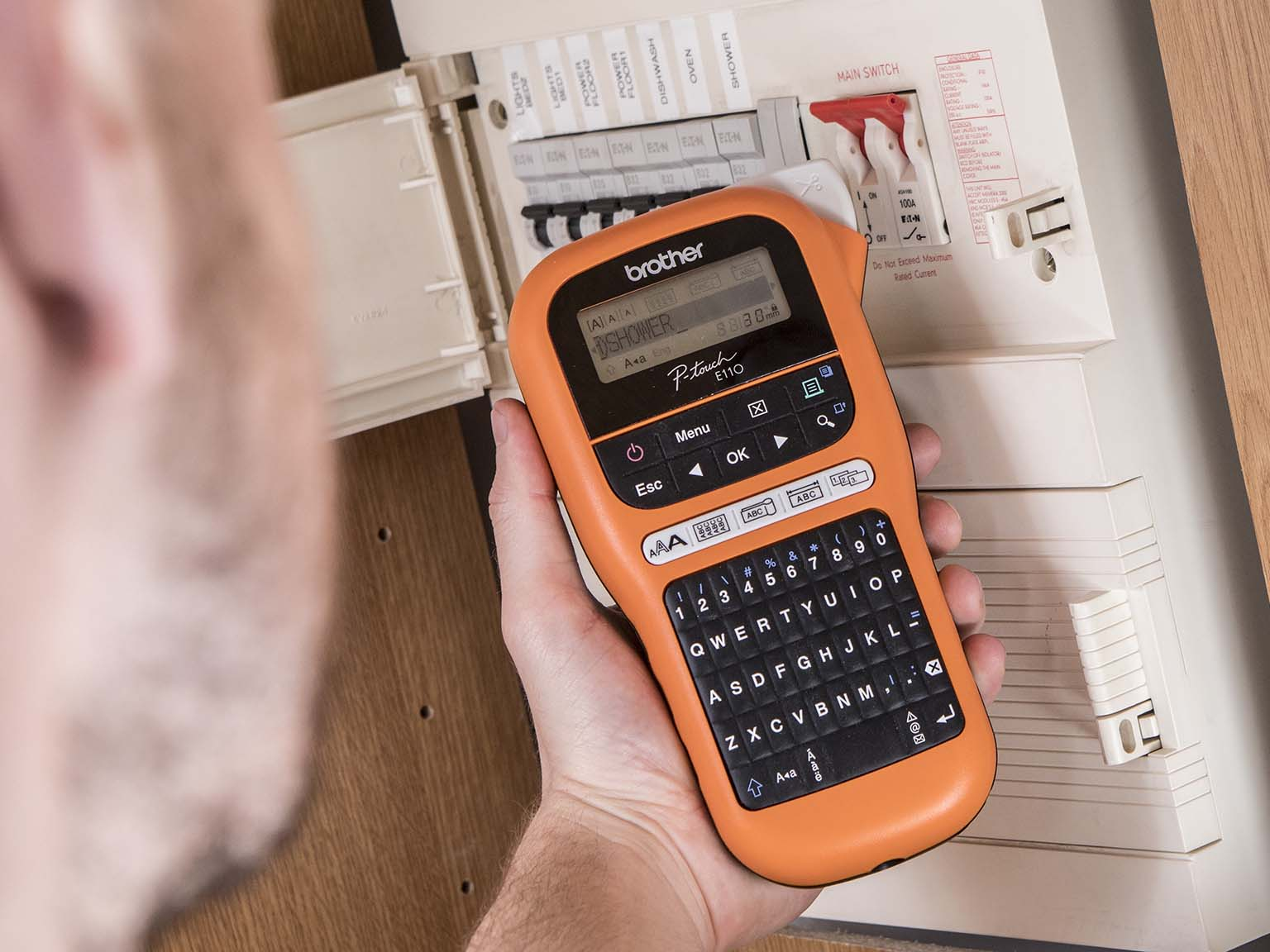 Brother P-touch E110 Beschriftungsgerät vor einem SIcherungskasten