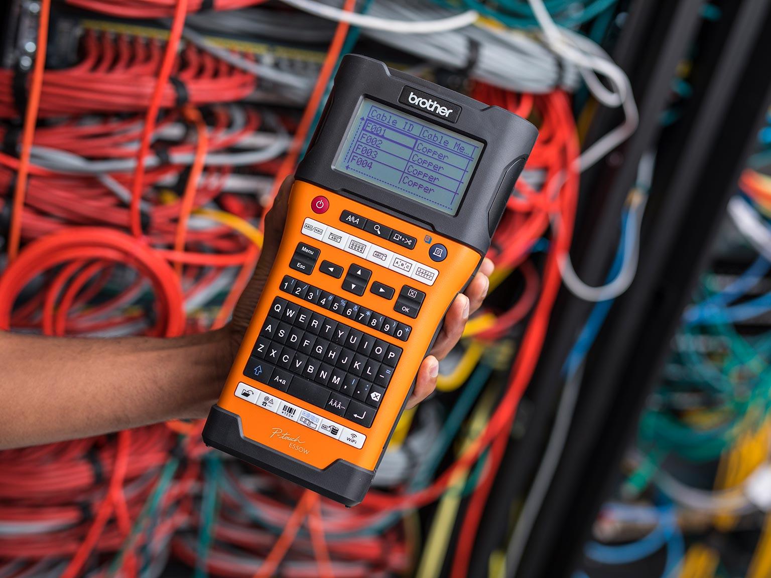 PT-E550W Beschriftungsgerät in der Hand vor Netzwerkkabeln gehalten