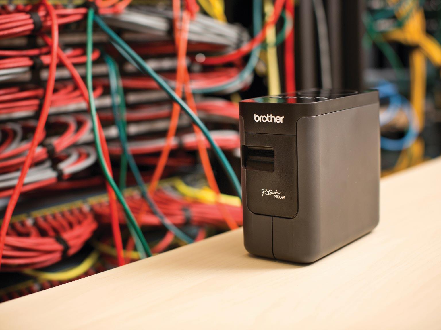 Brother PT-P750TDI Beschriftungsgerät auf einem Tisch vor Netzwerkkabeln
