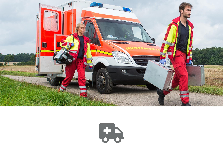 Rettungssanitäter mit Ausrüstung  auf einem Feldweg mit RTW