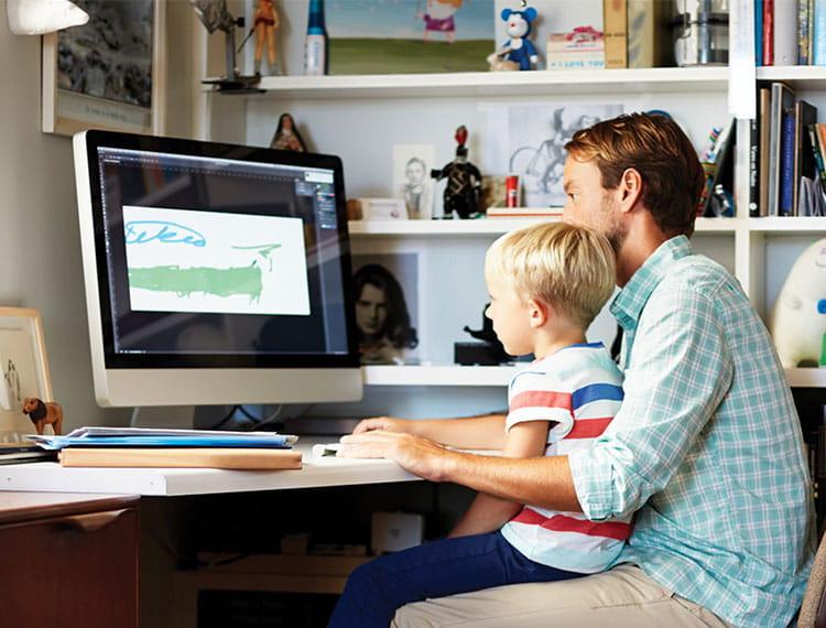 Vater mit Sohn vor Computer im Büro