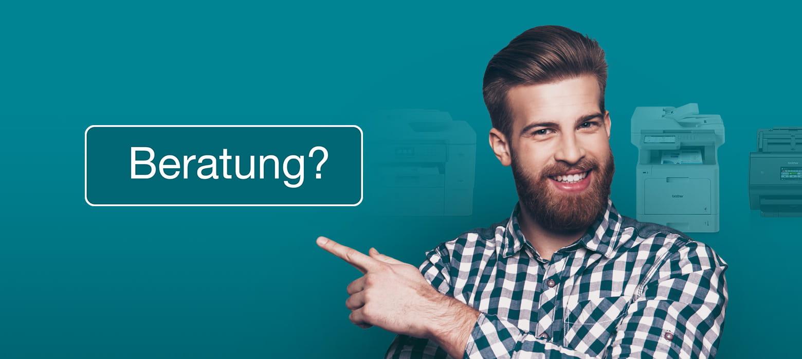 Mann mit Bart, lächelnd, zeigt auf Schild Beratung, Modelle im Hintergrund