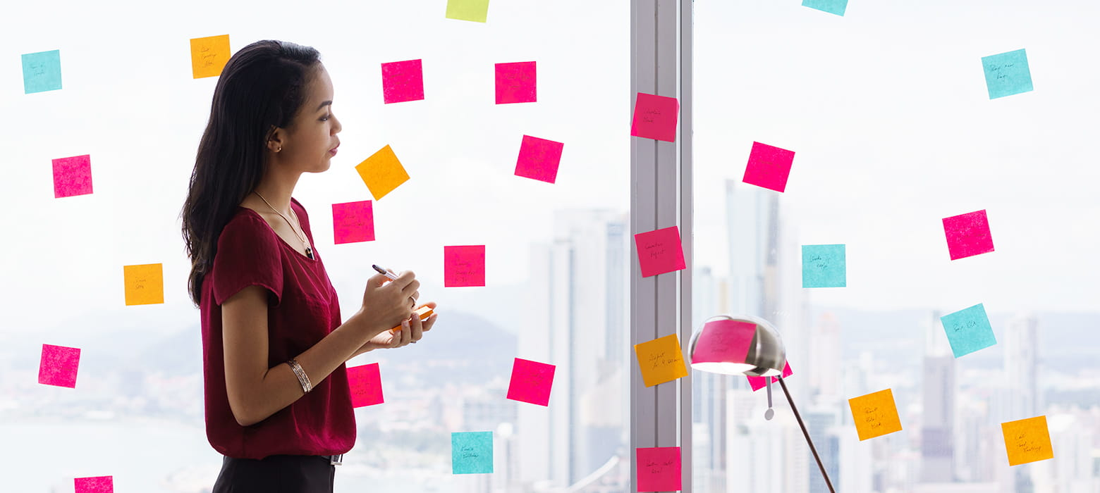 Frau klebt Post-Its mit Notizen an eine Fensterscheib