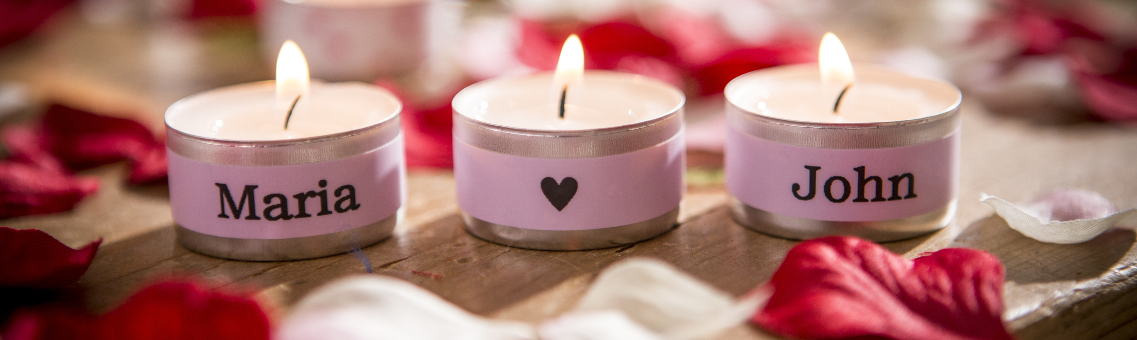 Lit candles personalised with names on a pink label using a Brother P-touch label and ribbon printer