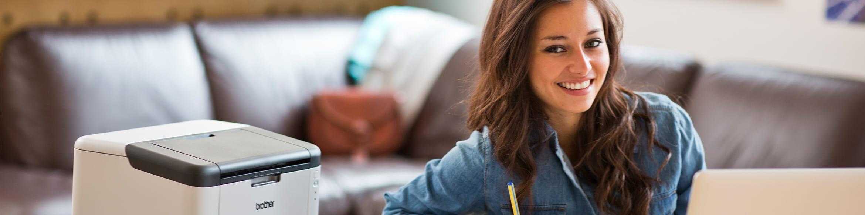 Junge Frau neben Drucker lächelt in Kamera