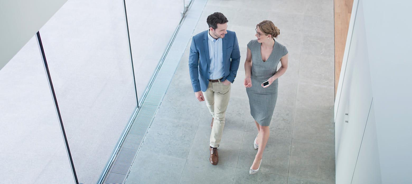 Mann und Frau unterhalten sich während sie einen Flur entlang laufen