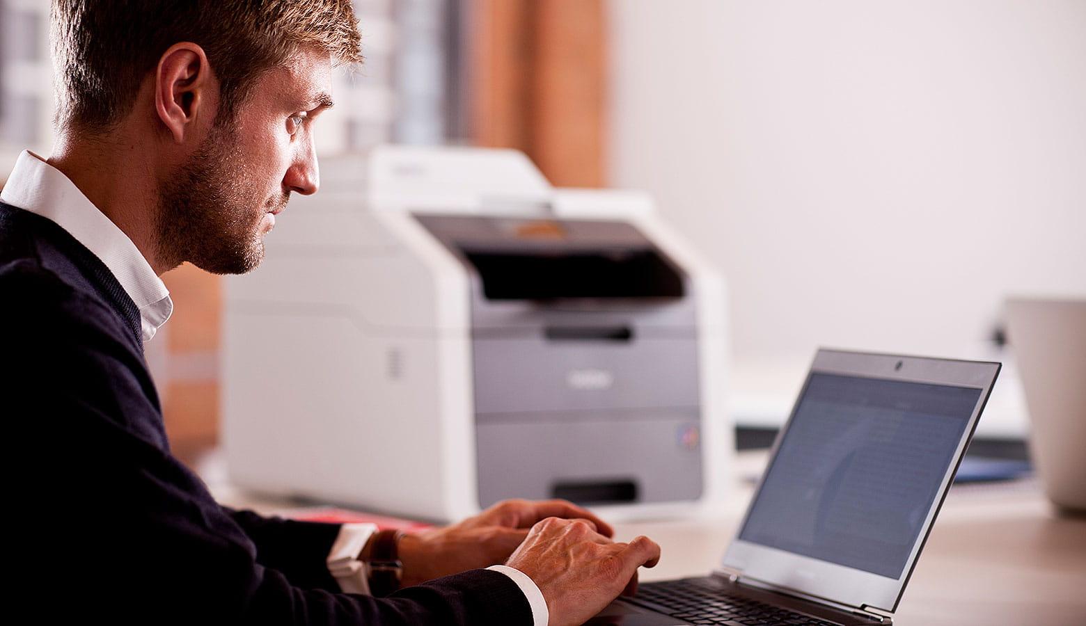 Kollege aus der IT-Abteilung sitzt vor seinem Laptop