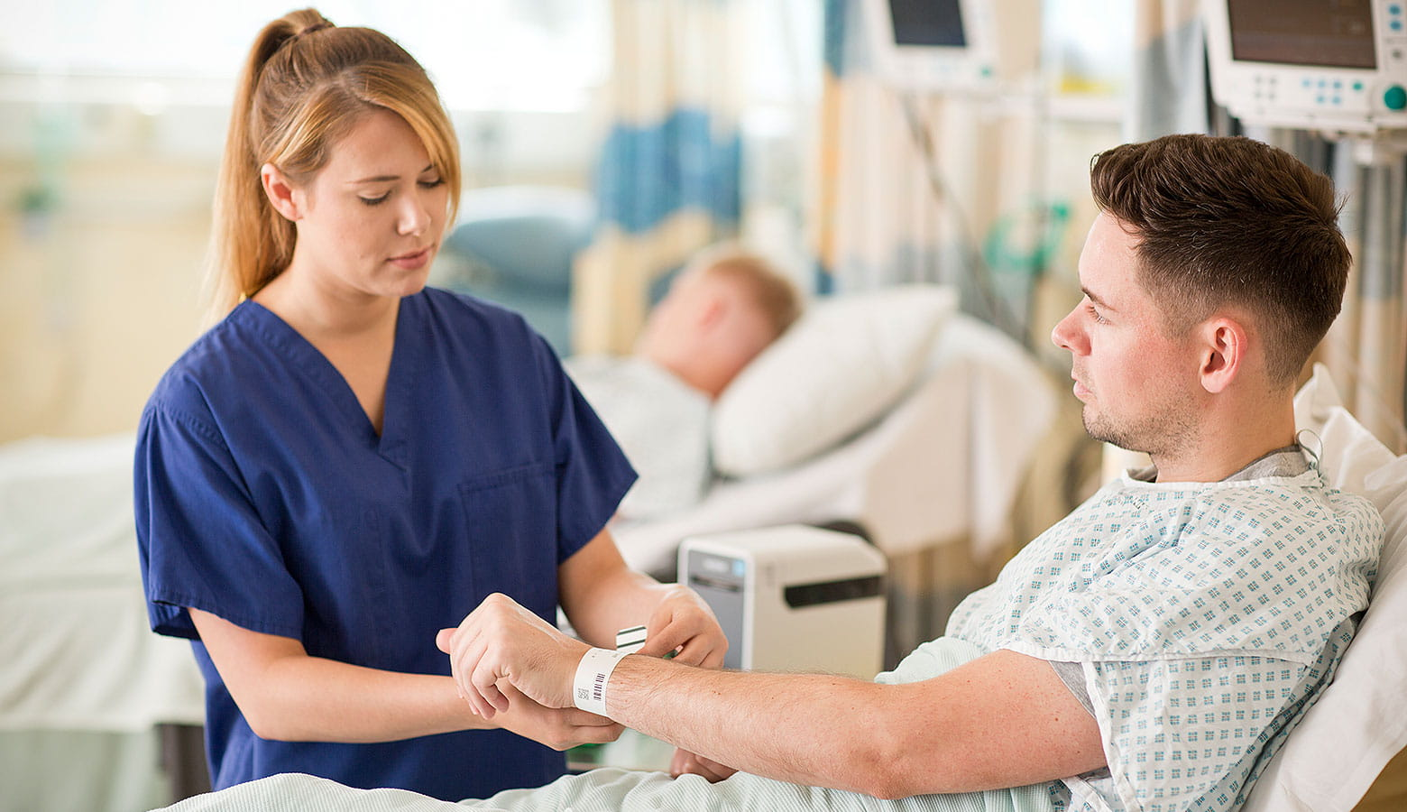 Kraneknschwester legt Patienten sein Armband an