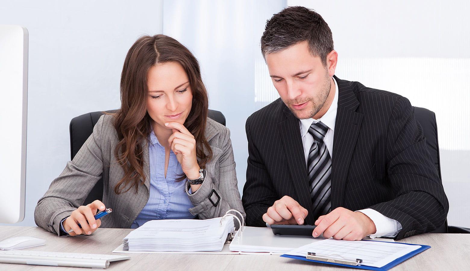 Zwei Kollegen aus der Personalabteilung sitzen gemeinsam über Dokumenten