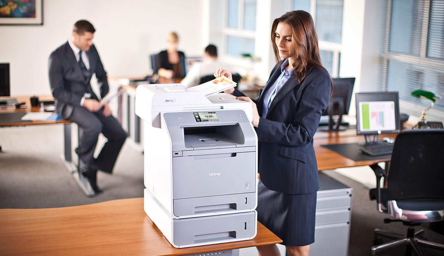Frau druckt am Abteilungsdrucker ihre Dokumente