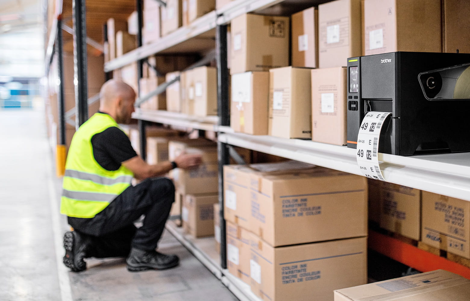 TJ-Etikettendrucker in Lagerregal mit Paketen, Lagermitarbeiter im Hintergrund