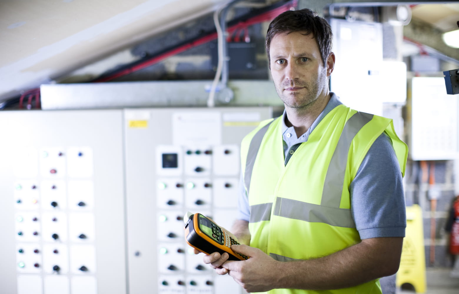Male electrician in front of a distribution board, holding a Brother P-touch label printer