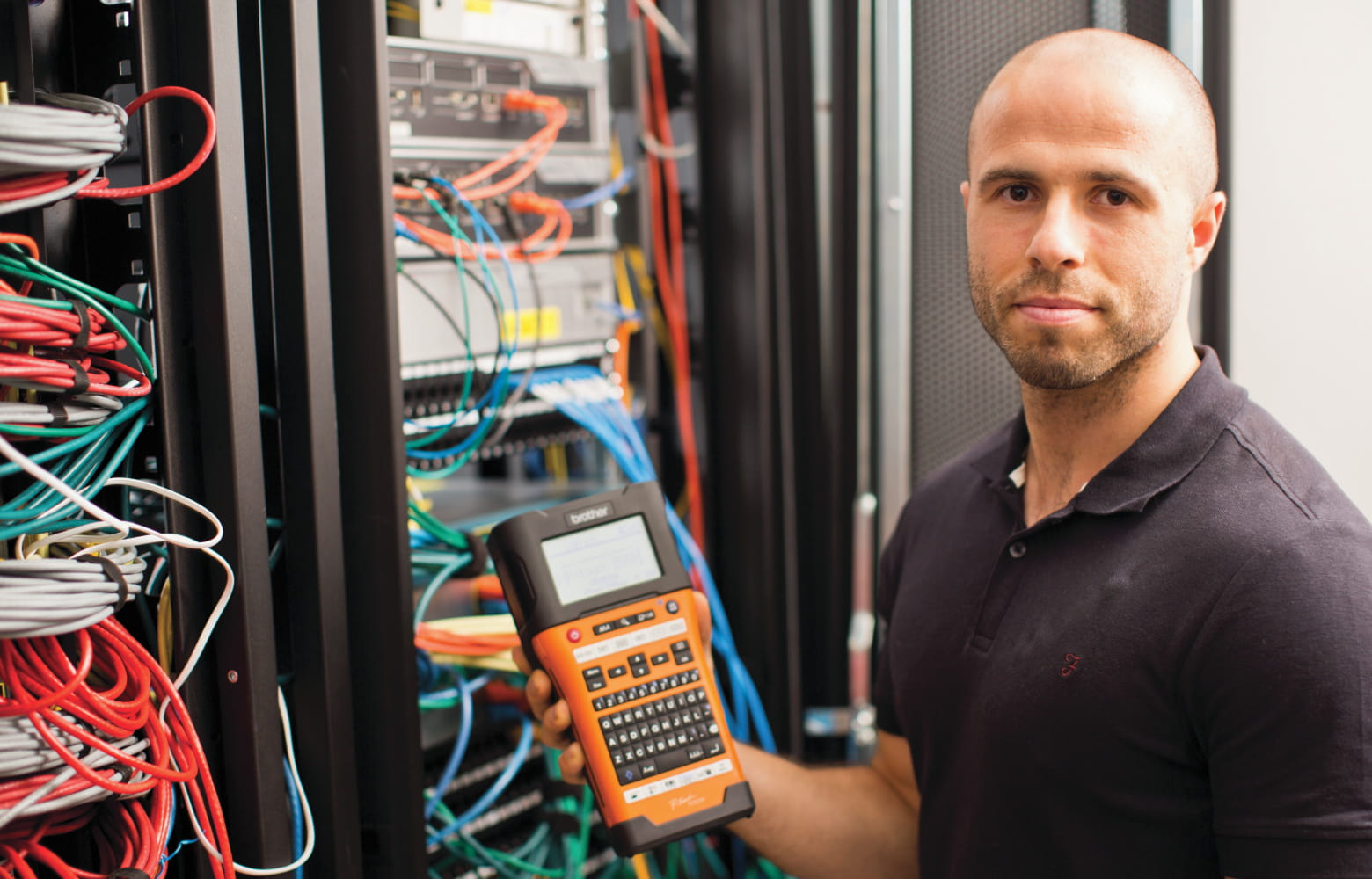 Male network technician stands in front of a neatly labelled network cabinet, whilst holding a P-touch label printer