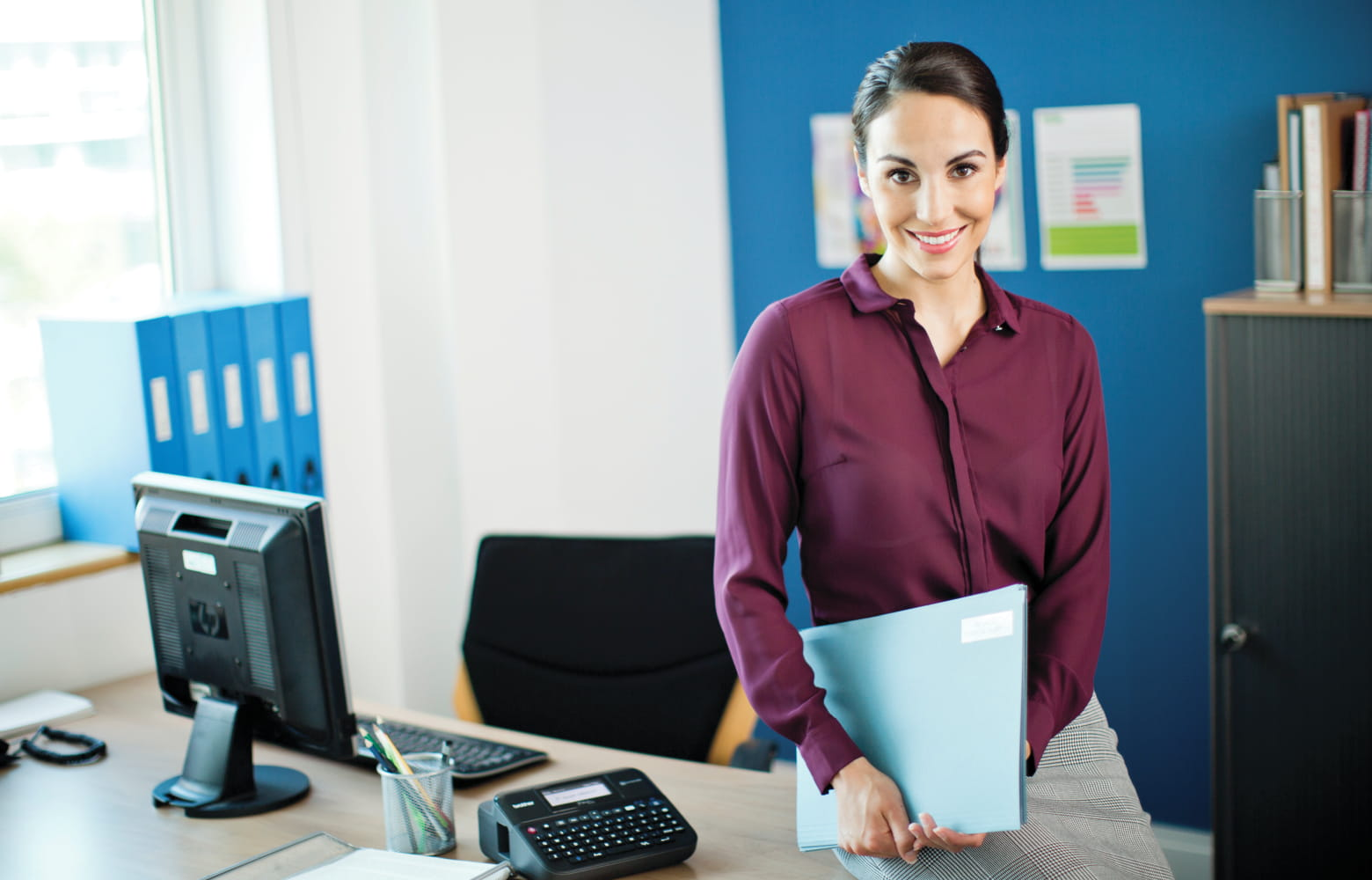 Female office worker sat on office desk with file folder in hand, next to a PC and Brother P-touch label printer