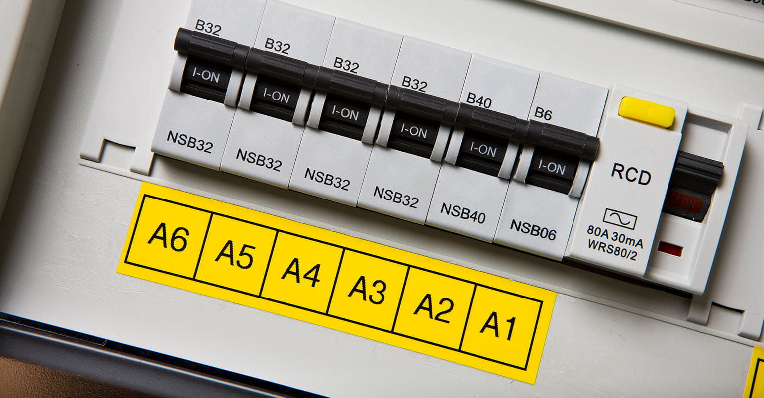 Consumer unit labelled with a Brother TZe yellow label