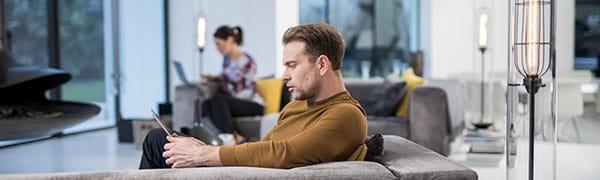 Mann sitzt auf einem Sofa und arbeitet an einem Tablet